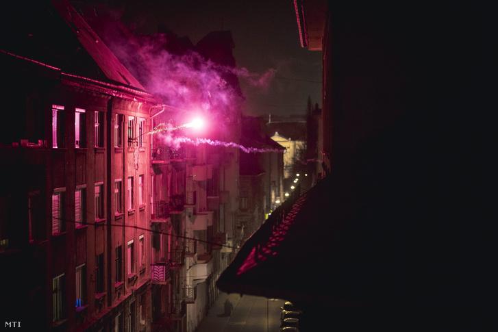Szilveszterezők tűzijátékot lőnek ki egy társasház ablakából Budapest belvárosában 2015. december 31-én.