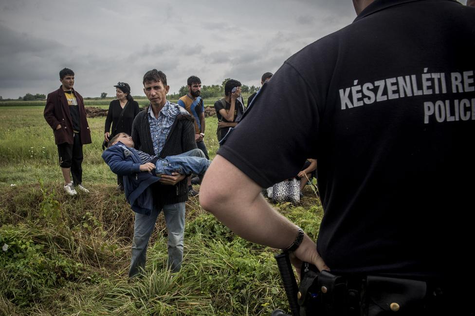 """A menekültek egy csoportját feltartóztatták a rendőrök a Röszke szélénél. A velem dolgozó angol újságíró épp a legszélső ház lakóját halgatta, akinek a szájából csak úgy ömlött a szó, és fennhangon szidalmazta a """"rohadtakat"""". Ekkor láttam meg én is illetve a felbőszült lakos is az apát, aki a kezében hozta a kritikus állapotban lévő gyerekét, akinek magas láza volt, és rángott a teste. Ekkor az addig anyázó ember teljesen átkapcsolt, és azonnal mentőt kezdett el követelni a totolyázó rendőröktől, mondván, a gyerek nem fogja túlélni a várakozást, láthatóan azonnali segítségre van szüksége. Végül az unszolására a rendőrök hívták ki a mentőt 1-2 percen belül. Hirtelen háttérbe szorult minden dogma és ideológia és átvette a helyüket a spontán, emberi reakció. Egyedülálló pillanat volt.                         2015 augusztus 15-én készült a kép a The Telegraph számára Röszke közelében."""
