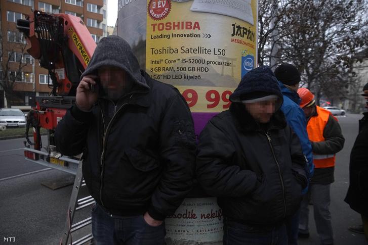 Egy örző-védő cég emberei a Mahír egyik hirdetőoszlopa előtt