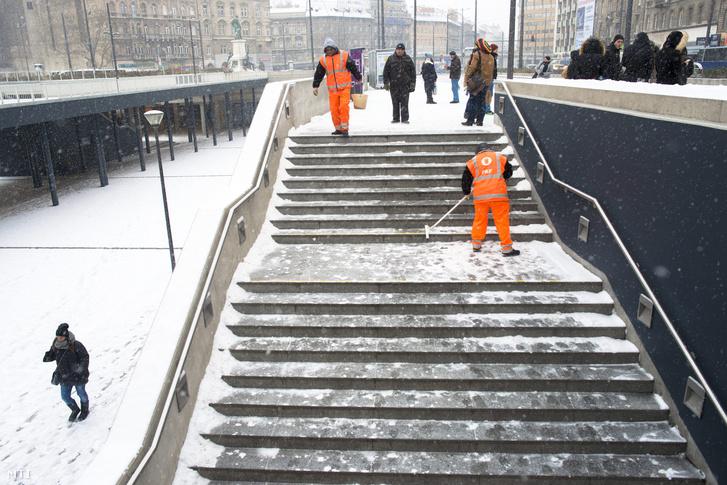 A Fővárosi Közterület-fenntartó Zrt. dolgozói takarítják a havat a lépcsőről a budapesti Keleti pályaudvarnál 2016. január 4-én.