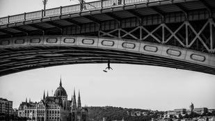 Fejjel lefelé lóg egy esernyős férfi a Margit hídról