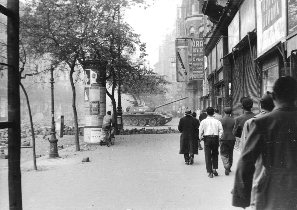 """1956. """"Járókelők"""" sétálnak az Erzsébet körúton látszólag olyan nyugalommal, mintha az ott előttük nem egy tank, csak egy kiforduló troli lenne. Csak a kerékpáros tűnik úgy, mintha fedezéknek használná a hirdetőoszlopot."""