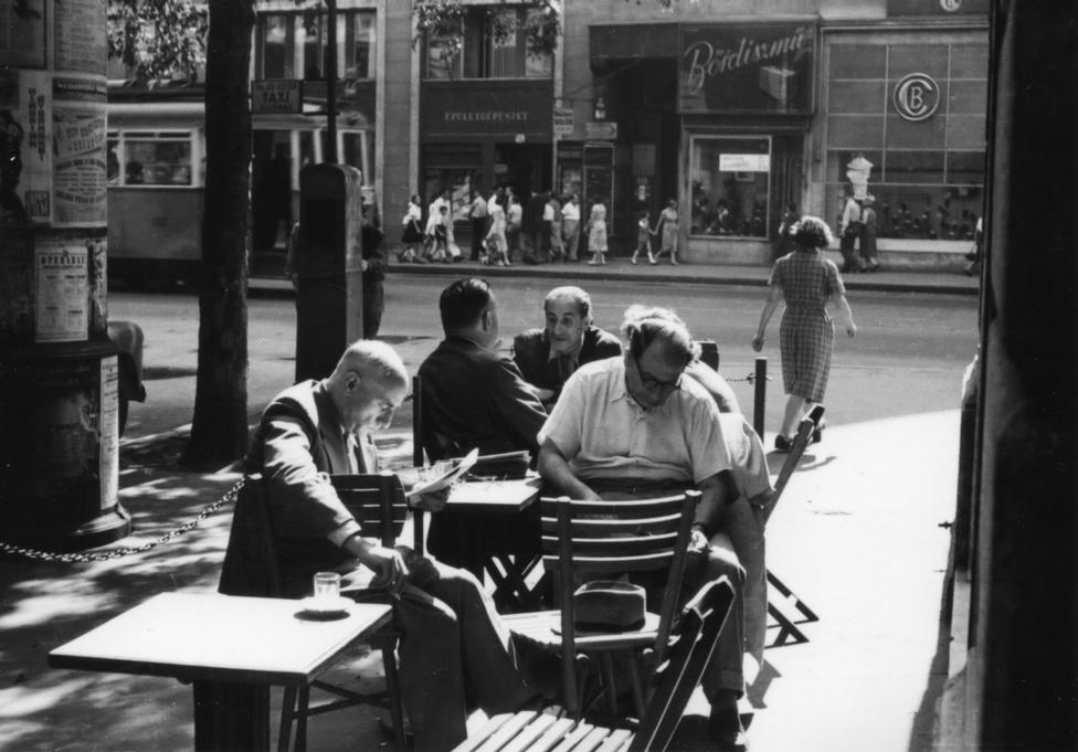 Amikor még vígan korzóztak az emberek a Kossuth Lajos utcában, s a Semmelweis sarkán az utcára kitett asztaloknál itták a feketét. A háttérben egy japán film és egy operabál plakátja. Mintha csak Olaszországban járnánk. Pedig azért 1955-ben nem lehetett valami vidám hely Budapest.