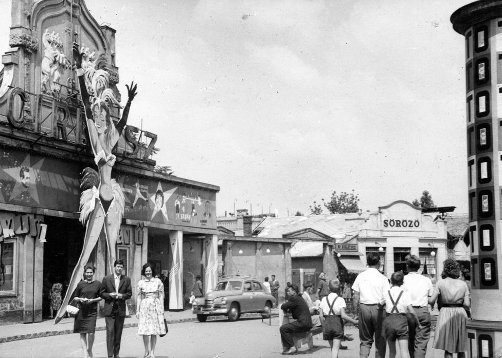 Bár a gigantikus szexi nővel nem versenyezhet, azért a Cirkusz előtti ligeti forgatagból sem hiányozhatott a hirdetőoszlop. 1964-ben épp egy jópofa totóhirdetés volt rajta, úgy néz ki vele, mintha valami op-art alkotás lenne.