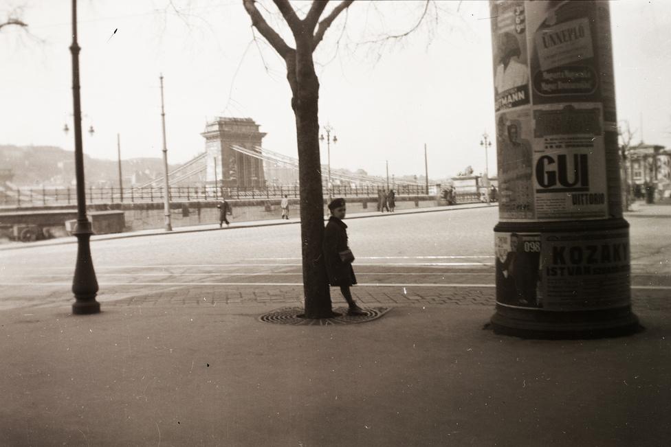Hirdetőoszlop a Lánchíd pesti hídfőjénél. A fának támaszkodó gyerek alatt egy legalább olyan ikonikus budapesti utcaelem van, mint amilyen az oszlop: a fák földtányérját védő vasrács. Ezen az 1941-es fényképen épp úgy néz ki, mint Fromm Géza 1894-es térhatású fotóján a Nagykörúton, vagy a mai Pesten bárhol.