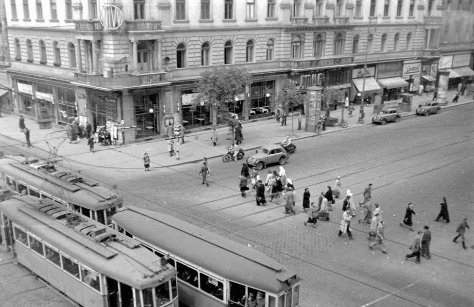 Sarokház a Nagykörút és a Rákóczi út kereszteződésében, a Blahán. Ezen az 1952-es képen még olvasható az EMKE felirat. A villamosok még mindkét irányban jártak, a zebrát még csak két pöttysor jelezte, nem volt se metró, se népszerűtlen árkádsor. Érdekes viszont a ház sarkán az első emelet magasságában kialakított, fedett forgalomirányító hely. Minket azonban persze a hirdetőoszlopok érdekelnek: ott van egyből kettő is. Túlélték a háborút, az államosítást - akkor épp az Állami Hirdető Vállalathoz tartoztak -, és mint látható, több fajtájuk is volt.