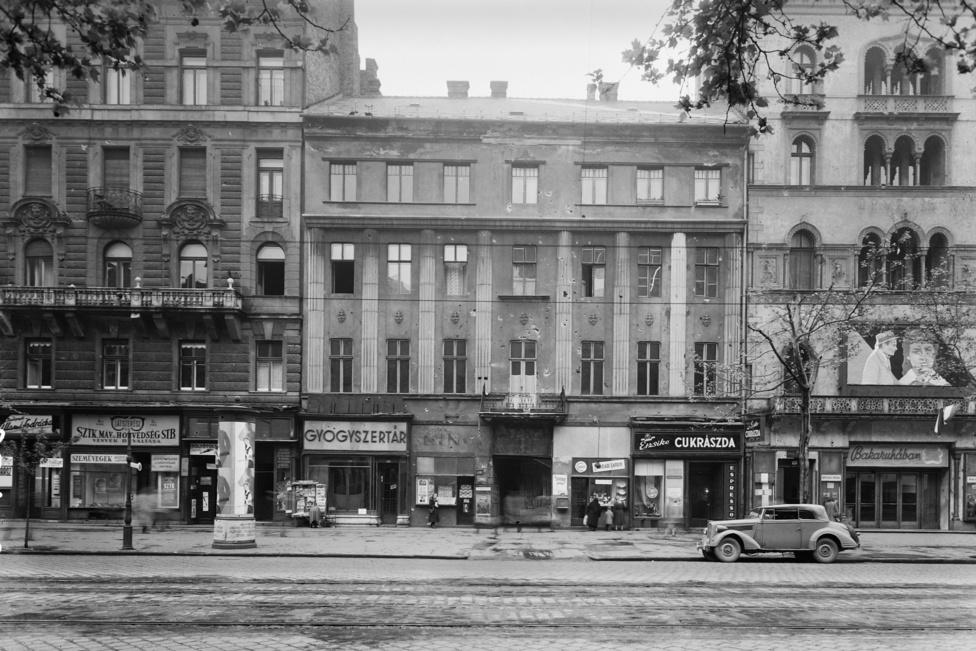 Egy évvel korábban még katonaruhákkal volt tele a város, ezen a fotón viszont már a Bakaruhában című, új magyar film plakátjait láthatjuk az Uránia mozi bejárata fölött éppúgy, mint a hirdetőoszlopokon. Ugyanebben az évben, 1957-ben alakul meg amúgy a Mahir, a Magyar Hirdető is.