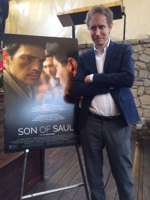 Nemes Jeles László az Egyptian Theatre épületében egy Saul fia plakát előtt