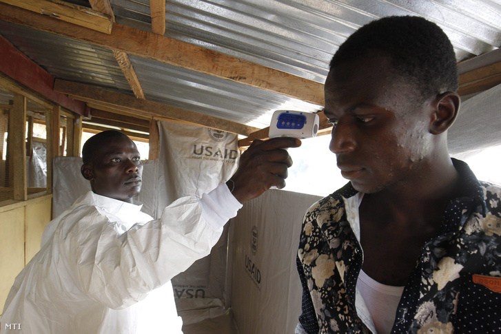 Egy libériai ápoló lézeres hőmérővel megméri a testhőmérsékletét egy férfinak egy monroviai kórházban 2015. november 26-án.