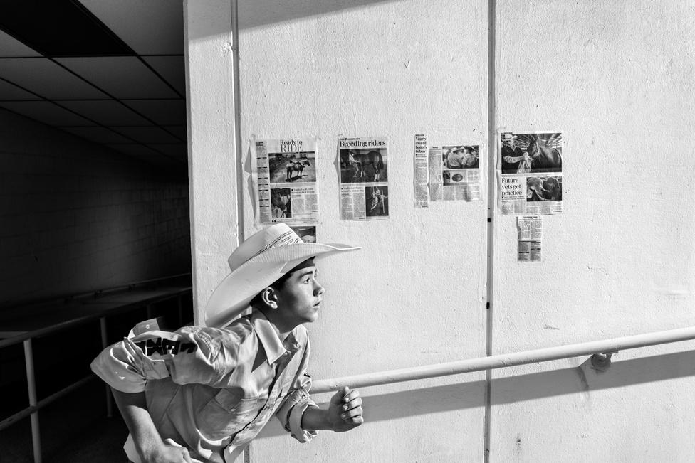"""Jonno Rattmant, a fotóst egy napon felhívta a New Yorker szerkesztője, és megkérdezte, szeretne-e rodeózó gyerekeket fotózni Abilene-ben. """"Persze, hol írjam alá?"""" - vágta rá Rattman. """"Tökéletes megbízás volt számomra"""" - írta az Indexnek. Úgy nőtt fel, hogy a nyarakat Montanában töltötte, szóval megfordult már jó pár rodeón, és ismerős volt neki a közeg. Fotózás közben igyekezett távol tartani magát a bikáktól: hatalmas és kiszámíthatatlan jószágok. Gyerekkorában arcon rúgta egy ló, akkor megtanulta, hogy tartsa tiszteletben az állatokat. Amikor készült a fotósorozat, felült azért egy műbikára az egyik versenyző otthonában. Nem húzta soká, amikor feltekerték a sebességet."""