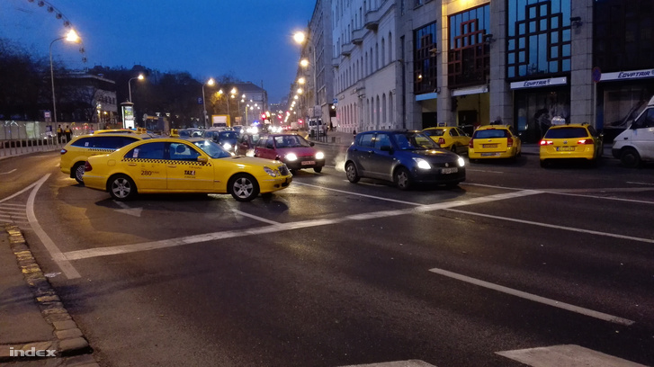 Taxik parkolnak a szélső sávokban a kereszteződés mindkét oldalán.