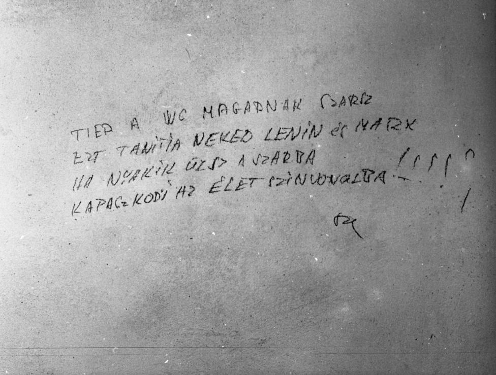 Az elkövető ezt graffitizést biztos nem úszta meg szárazon, hiszen még szignózta is a rendszerkritikát. Legalább így fennmaradt az utókor számára.
