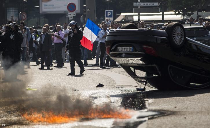 Rohamrendőrök egy felborult autó mellett a párizsi taxisofőröknek az okostelefonra letölthető közösségi utazásmegosztó szolgáltatás tulajdonosa az amerikai Uber vállalat elleni tüntetésén 2015. június 25-én.