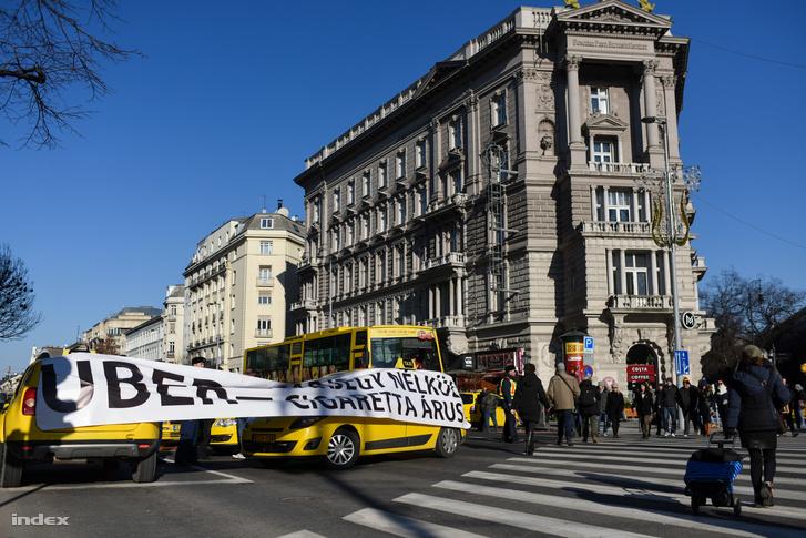 """""""Uber = zárjegy nélküli cigaretta árus"""" - áll a felirat a budapesti Deák téren tiltakozó taxisok egyik molinóján, 2016. január 18-án."""