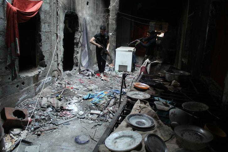Felkelők járőröznek egy lerombolt Der Ez-zóri ház romjai között (2014.)