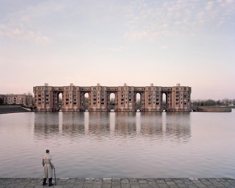 A Les Arcades du Lac-hoz hasonlóan a Le Viaduc szintén Ricardo Bofill tervei alapján épült fel, 1978 és 1982 között. A spanyol építész szándéka az volt, hogy Montigny-le-Bretonneu lakóinak környezetem mindennapi életük helyszíne is legyen legalább olyan impozáns és magasztos, mint a Versailles-ban élőké. Laurel Kronental 2015-ben készítette ezt a képet a Le Viaduc impozáns épületsorát fürkésző, 82 éves Jacques-ról.