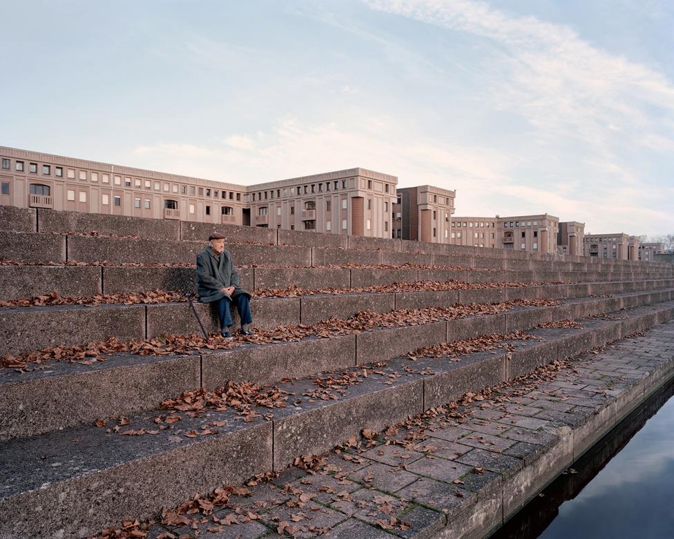 Párizstól délnyugatra, Yvelines megyében, Montigny-le-Bretonneux-ban szintén megfigyelhető a városképen Ricardo Bofill erőteljes kézjegye. A Les Arcades du Lac elnevezésű épületsor a szomszédos város, Versailles híres kastélyainak modernizált mása, kiegészítve egy hatalmas mesterséges tóval. Ezen a megkapó hangulatú, 2015 őszén készült képen egy helybéli, a 85 éves Roland töpreng az élet nagy kérdéseiről.