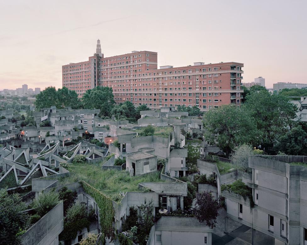Ivry-sur-Seines Párizs délkeleti agglomerációjának része, itt épült fel 1979 és 1982 között egy csupa teraszos, tetőkertes, girbegurba házlabirintus. Jean Renaudie ezzel a megoldással a természetet akarta harmóniába hozni az épített nagyvárosi környezettel, ahol a lakók a közösségi tetőkerteken aktív közösségi életet élhettek - éles kontrasztot alkotva a háttérben magasodó, vörös óriással, ami Henri és Robert Chevallier tervei alapján épült az 50-es években. Ön megtalálja a 81 éves Denise-t ezen a tavalyi fotón?