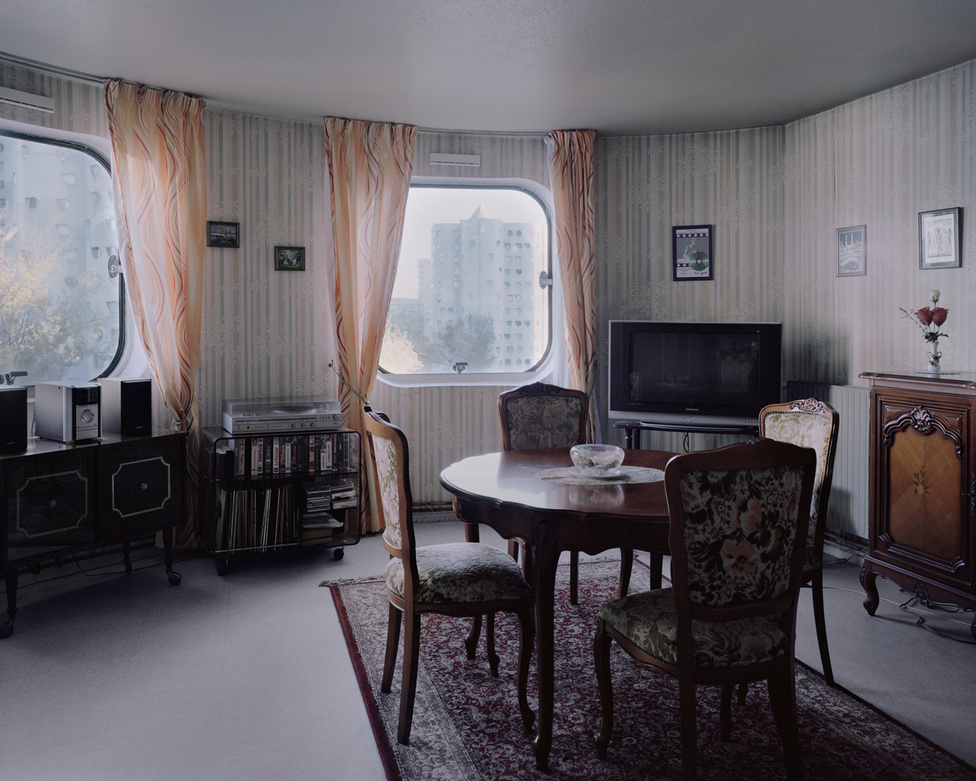 A nanterre-i Picasso-város egyik elegánsan puritán lakása, ahol jól megfér egymás mellett a praktikusan szép biedermeier bútor és a plazmatévé. A fotó ugyan 2014-es, de az időtlenséget sugárzó szobabelső, ami a fotóriporter Kronentalt is teljesen lenyűgözte, akár egy futurisztikusan retró sci-fiben is megállná a helyét. Szinte már várjuk, hogy bejöjjön Jules Verne vagy Conan Doyle, és lelkesen mesélni kezdjen a következő kalandregénye dinoszauruszokat kergető, Holdra utazó, víz alatti városokat felfedező hőseiről.