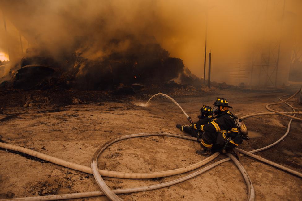 Tűzoltók próbálják kordában tartani a tüzet, ami egy helyi siló melletti szénakazalnál pattant ki, teljesen spontán módon.