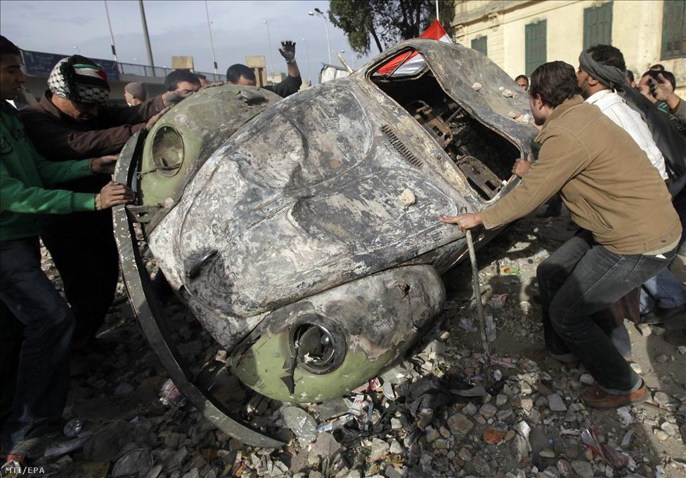 Kairó, 2011. február 3. Kormányellenes tüntetők egy kiégett járművel barikádot emelnek a kairói Tahrír tér közelében 2011. február 3-án, amikor ismét összecsaptak Hoszni Mubarak egyiptomi elnök hívei és a lemondását követelő tüntetők. A két tábor kövekkel, benzinespalackokkal dobálta egymást. Az utcai harcokban legkevesebb két ember életét vesztette. A 30 éve hatalmon lévő Mubarak rendszere ellen január 25-e tüntetnek Egyiptomban. (MTI/EPA/Felipe Trueba)