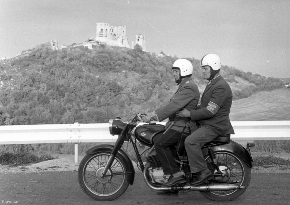Az 1980-ban készült fotón motoros rendőr viszi az önkéntest rendőrt, mögöttük a Cseszneki vár.