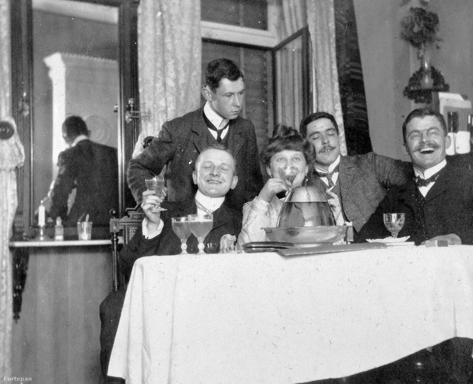 """Étteremben ünneplő társaság 1915-ben. Még tartott a """"nagy háború"""" optimista időszaka, mindenki azt várta, hogy Ausztria-Magyarország és a német császár seregei őszre Párizsba érnek, pedig a frontok már kezdtek beállni. A besorozott katonáknak tilos volt az alkoholfogyasztás, de az otthon ünneplő polgárságot még semmi sem gátolta ebben. A magyar szeszipar szépen fejlődött: a XIX.-XX. század fordulóján megépült a magyar sörváros Kőbányán. A magyar sörgyár már 3 millió hektó italt értékesített. Ferencváros külső részén pedig az 1840-ben alapított Zwack márka terjeszkedett és kezdett gyárépítésbe. És ez az időszak, amikor a Tabán helyén még borváros létezett: svábok árulták a Budai-hegységben és a Pilisben termesztett boraikat, mindössze 5-10 perc villamosozásra a belvárostól. Itt ivott Krúdy Gyula írónk is, aki sokszor ki se mozdult az itteni kocsmákból: novelláiért futárt küldtek az előző után járó fizettséggel, amivel folytathatta a mulatást. Ha elfogyott a pénze, egy újabb anekdotát vetett papírra. """"Kis üveg borok és pálinkák vándorolnak a bundazsebekbe, a bajuszok a legkülönbözőbb vidéki zsíroktól fénylenek, de a szívet már némi nyugtalanság háborgatja az esetleges lemaradás miatt"""" – írta Isten veletek, boldog Vendelinek című novellájában, amely a legenda szerint a Mélypince nevű italozóban keletkezett az 1910-es években."""