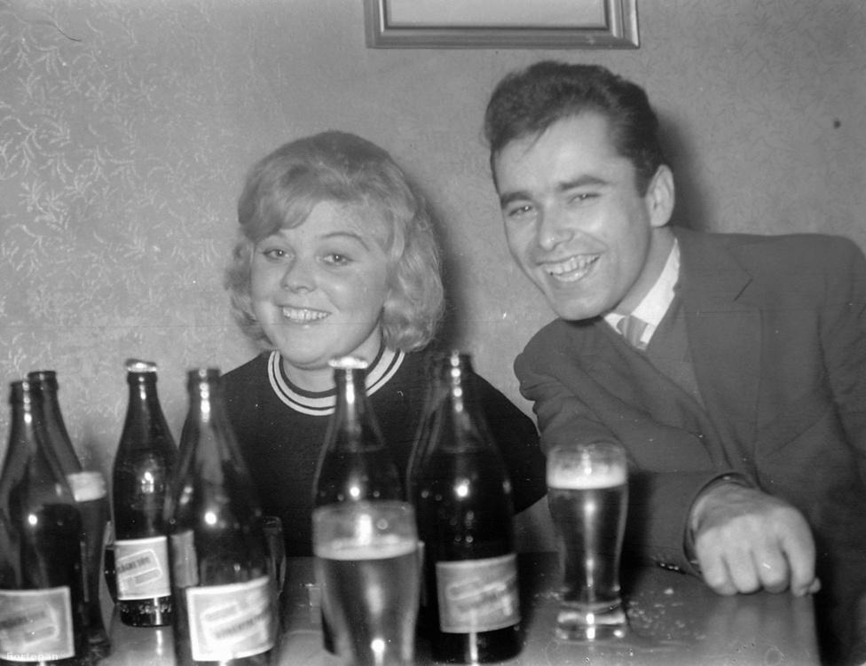 """Szalon sört ivó pár 1961-ben. A szocializmusban az itthon fogyasztott söröket Magyarországon is gyártották. A '60-as évek legjobb sörének a """"Soproni Ászokat"""" tartották, de népszerű volt a Pécsi Szalon és a Balatoni világos is. Az ország keleti részében a Borsodi volt a legnépszerűbb, ez viszont nem jutott el a Dunántúlra. Utóbbi fél litere a '60-as években 3 forint volt, a mostani söröknél majdnem kétszer több szénsavat tartalmazó Rocky Cellarért 4,5-6 forintot kértek el, a Kinizsi a Kőbányai 3,5 forintba kerültek."""