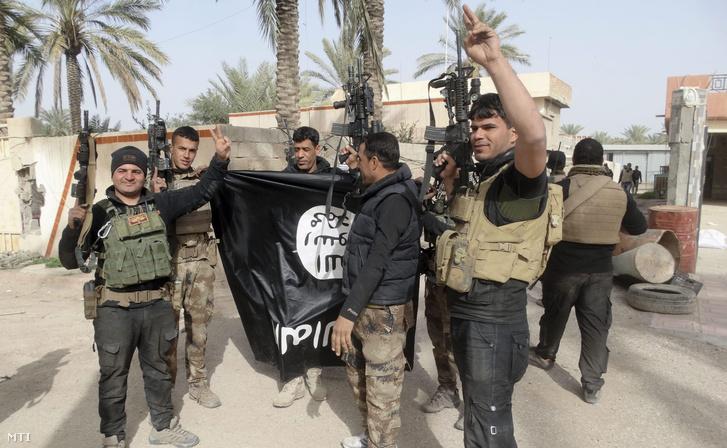 A 2016. január 21-én közreadott képen az iraki kormányerők tagjai az Iszlám Állam szélsőséges dzsihadista szervezet elkobzott zászlaját mutatva ünnepelnek a közép-iraki Ramádiban január 19-én miután visszafoglalták a stratégiai jelentőségű város központját az Iszlám Állam fegyvereseitől.