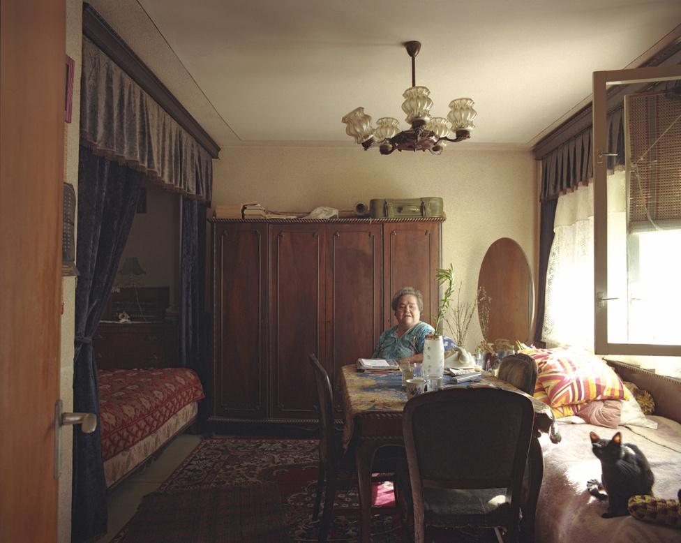 A fotós készítette alaprajz szerint a 10/1-es ház lakásai így néznek ki: ha az ember belép az ajtón, bal kéz felé esik a szoba, jobbra a fürdő és a konyha. A szoba alapja egy nagyjából négy és félszer négy és fél méteres négyzet, de az egyik sarkából lecsíp az előszoba. Az egész lakás összesen úgy 28 négyzetméter.                         A nyugdíjas Suhariuc Ioana asszony baldachinos ágyára a magyarázat: a ház közel van a piachoz, és ő néha szállást ad olyanoknak, akik a piacra mennek árulni. A vendégek alszanak a baldachin alatt, ő meg az ablaknál lévő ágyon. 1967 óta itt lakik, 1982 óta egyedül, leszámítva a macskát, aki 1989-ben csatlakozott hozzá.