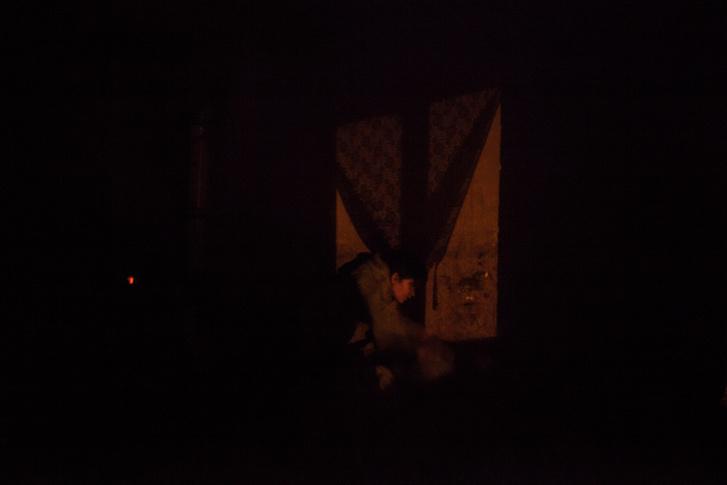 Az utcalámpa fénye befelé vet árnyékot, miközben Éva lázas gyermekének hőmérsékletét ellenőrzi.