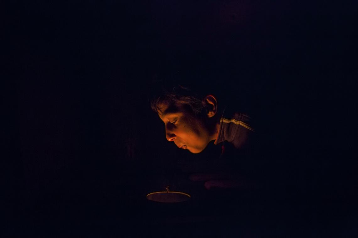 Az egyetlen fényt adó kályhában igyekszik felcsiholni a tüzet egy fiú. |