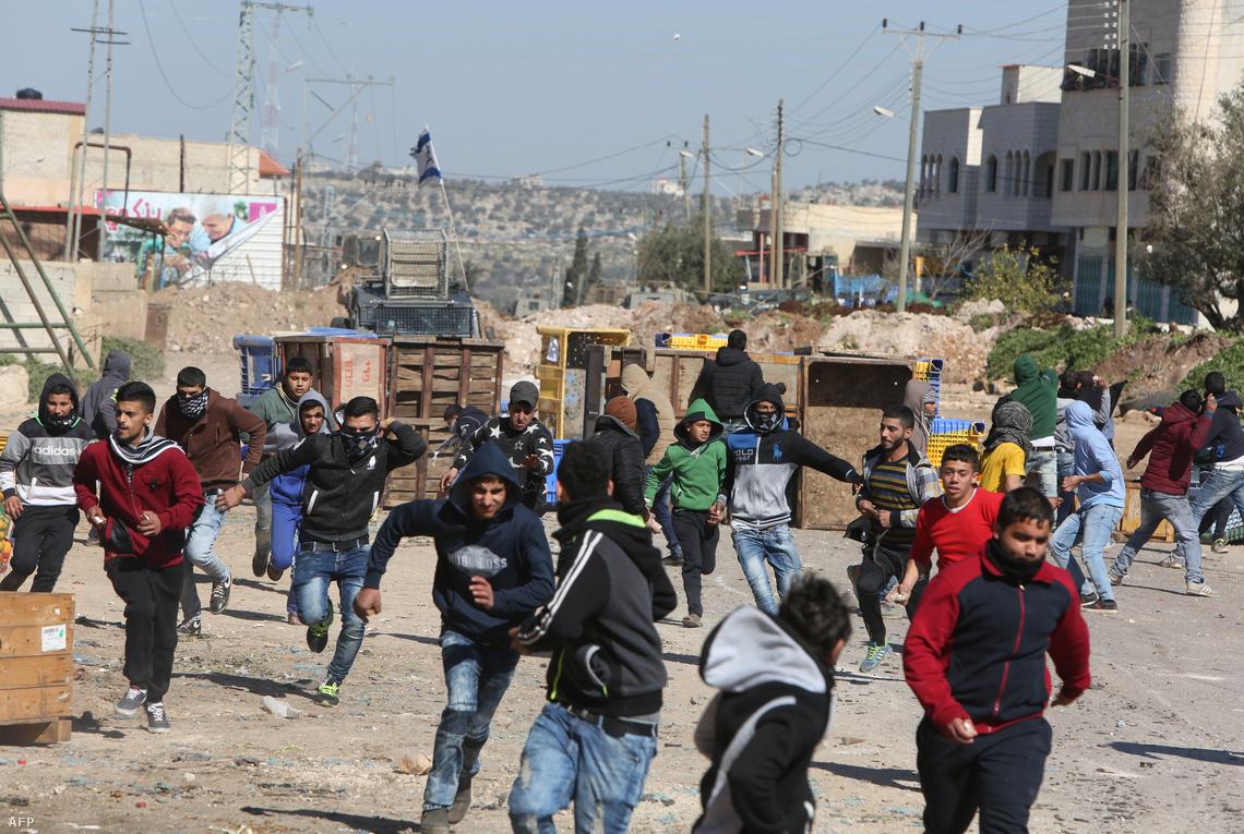 Palesztin fiatalok futnak az izraeli hadsereg elől egy utcai összecsapás végén a Gázai övezetben