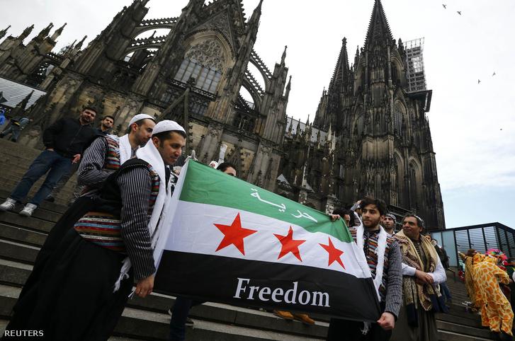 Szír menekültek feszítették ki a szír zászlót a kölni Katedrális előtt, 2016. február 8-án.