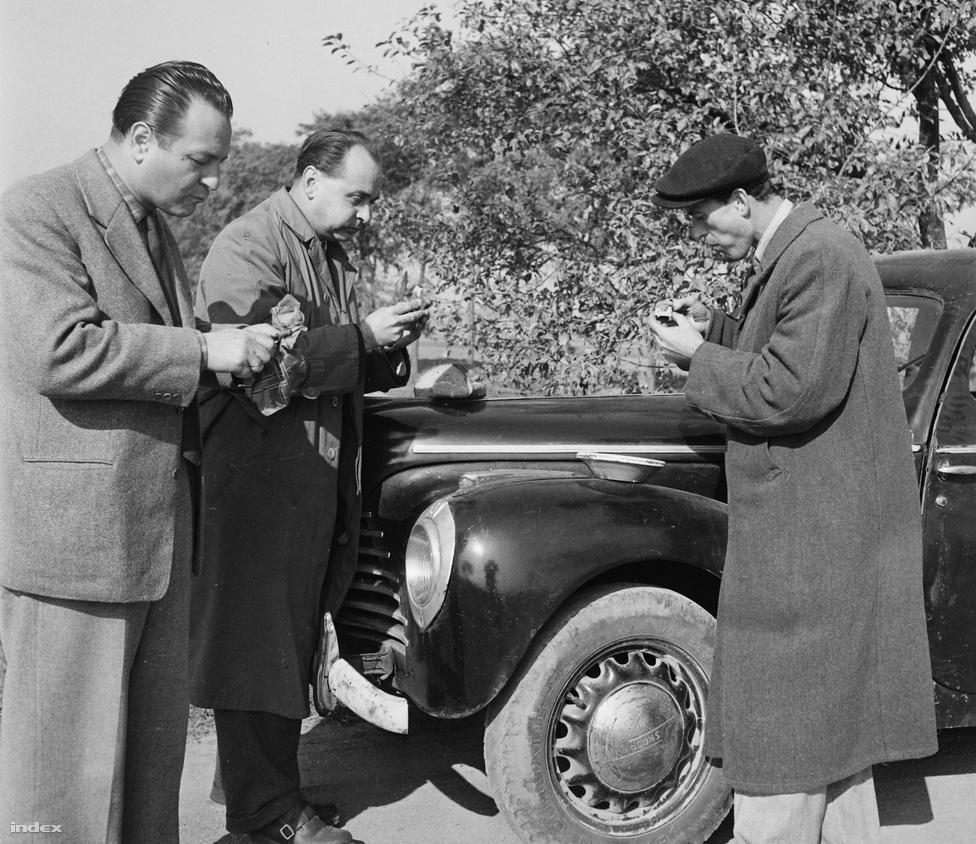 Hátranyalt hajú férfiak falatoznak egy fekete motorháztető körül. Talán egy vidéki riportra tartanak épp autóval?