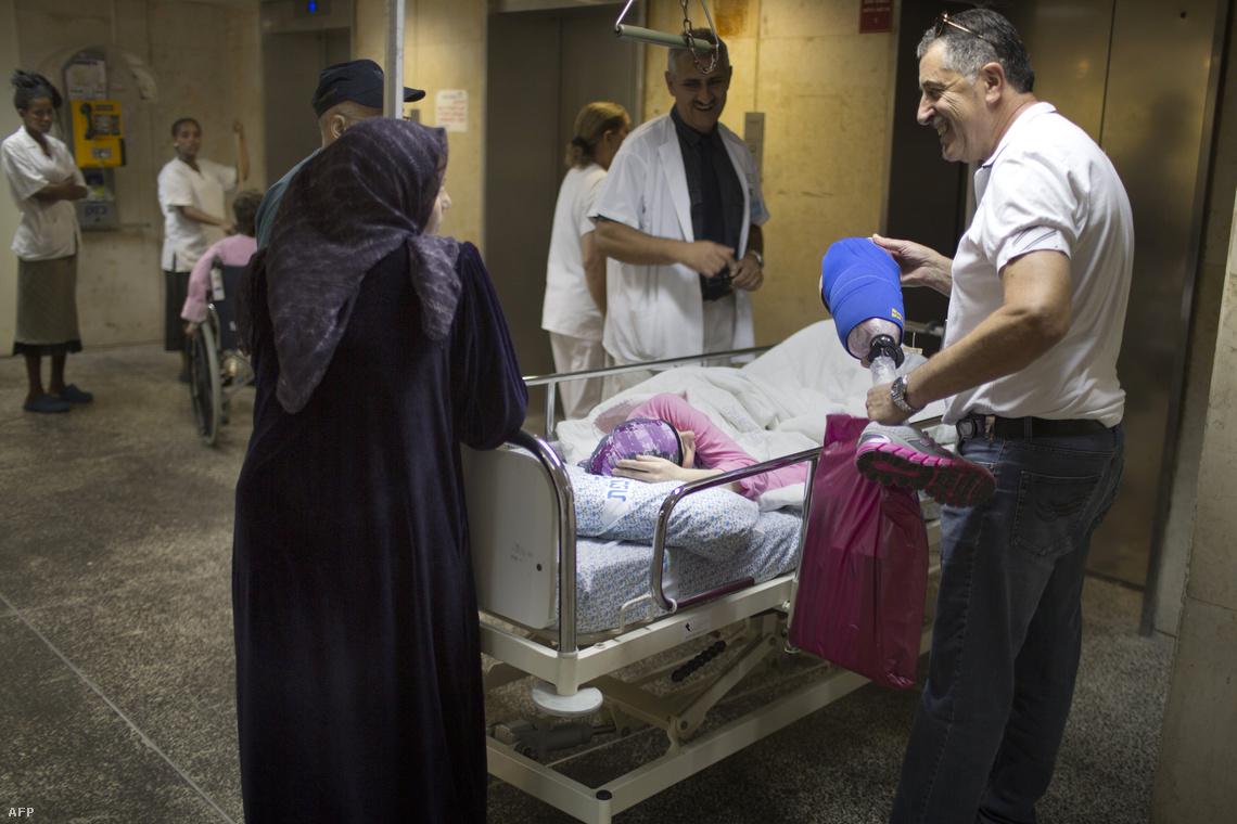 Egy izraeli orvos műlábat mutat egy rakétatámadásban megsérült szíriai kislánynak, akinek amputálni kellett az egyik lábát. A Ziv kórházban készült képen hátul Alexander Lerner professzor látható.