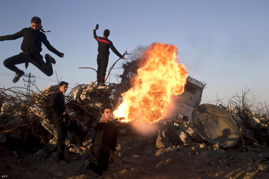 Palesztin fiatalok játszanak a tűzzel egy 2014-ben lebombázott ház romjai között a gázai övezetben.