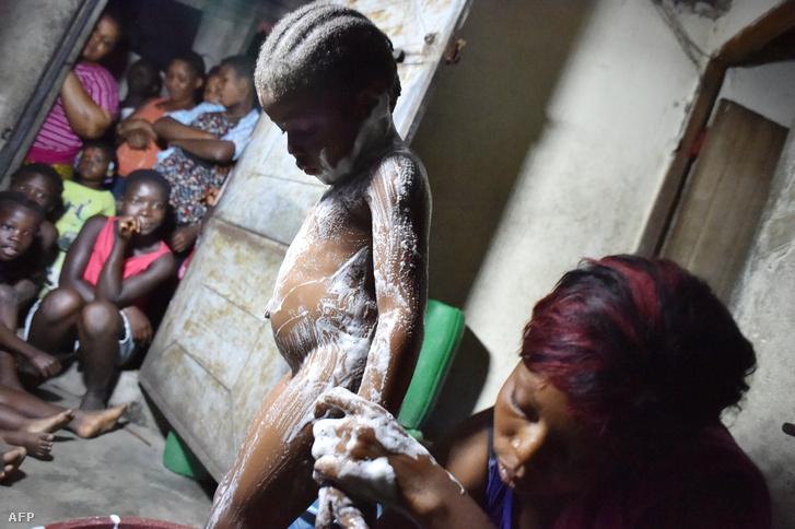 Egy anya mosdatja a fiát Libériában, ezzel védekezve az ebola ellen