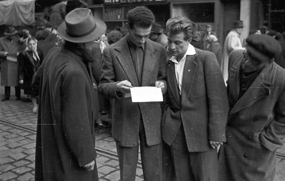 Szellem és Kenyér. Röplapolvasók a Visegrádi utcában, a háttérben egy vidékről érkezett teherkocsiról élelmiszert osztanak.