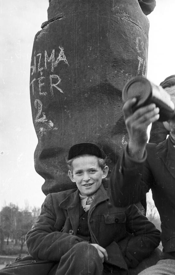 """Kissrác a ledöntött Sztálin szobor maradványán, a """"Csizma tér 2""""-n. Sztálin Blaha Lujza térre vontatott testét ekkorra már                          feldarabolták a járókelők."""