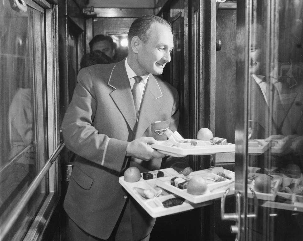Egy pillanatra olyan benyomása van az embernek, mintha maga a fiatal Kádár János szolgálná fel a praktikusan formatervezett tálcákon az ételt. Persze nemcsak ez a hihetetlen elem ezen a képen, legalábbis a vonatozók nagy tömegeinek. Ez a vasúti utasellátást bemutató életkép ugyanis szintén olyan színvonalról mesél, amilyennel a nyolcvanas években már nem találkozhattunk. Minden valószínűség szerint a hatvanas-hetvenes években készült, és az első osztályú hálókocsik utasainak járt ez a fajta kitüntetett figyelem.