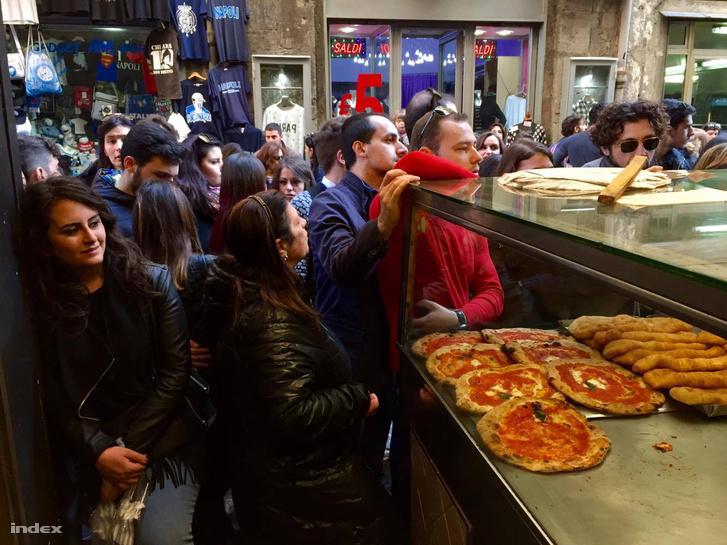 Tömött sorokban várják a pizzát egy utcai pizzéria előtt Nápolyban
