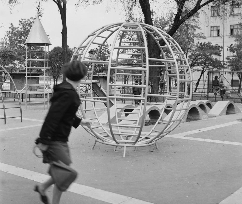 Bodolai László: A gömbmászóka háttérben a rakétával valószínűleg a szovjet űrkutatás nagyságát szimbolizálja, ahogy Gagarin a Vosztok 1-el elsőként megkerülte a Földet. A rakéta mellett látható még a harmadik klasszikus játszótéri elem, az elgörbített létra  alakú mászóka is. A három játékot nehézségi fokozatonként is differenciálhatjuk. A gömb mászókán játszani nem volt túl nagy kihívás, ha belül megcsúsztunk, nem az aszfaltra, hanem gömb alsó részére estünk, ami valamelyest tompított a bbecsapódáson. A rakéta 3-4 méteres magasságával már korhatárhoz kötött volt, az igazán menők felültek a rakétafejre, és onnan lógatták a lábukat, amely valljuk be, nem tűnt veszélytelen mutatványnak, mivel a rakétát is aszfaltra állították. Az űrhajós kiképzés részeként az egyensúlyérzékünket  a félkörbe hajlított létra  mászókán lehetett leginkább fejleszteni, én 9 évesen tudtam először kapaszkodás nélkül végigsétálni rajta. A propagandasztikus játékelemek álltak távol a korszellemtől, a katonai bölcsődében, ahová Veszprémben  bekerültem, - apám pilótaként szolgált - egy kibelezett MÍG 17-es repülő volt az fő mászójáték, soha nem felejtem el életem első üzletét, az akkori szerelmemmel, Belány Ildivel a gép törzsében a hajtómű helyén üldögélve elcseréltük a műanyag napszemüvegeinket egymással. Később több helyen találkoztam kibelezett vadászgéppel, mint játszótéri játékkal, például Kecskeméten a Műkertvárosban,  vagy a mezőhegyesi strand mellett.  A hidegháború enyhülése a játszóterekre is kihatott: a 80-as években a szintén kecskeméti Széchenyi lakótelepre rakéták helyett felpúpozott  hátú macskafigura  mászókákat telepítettek.