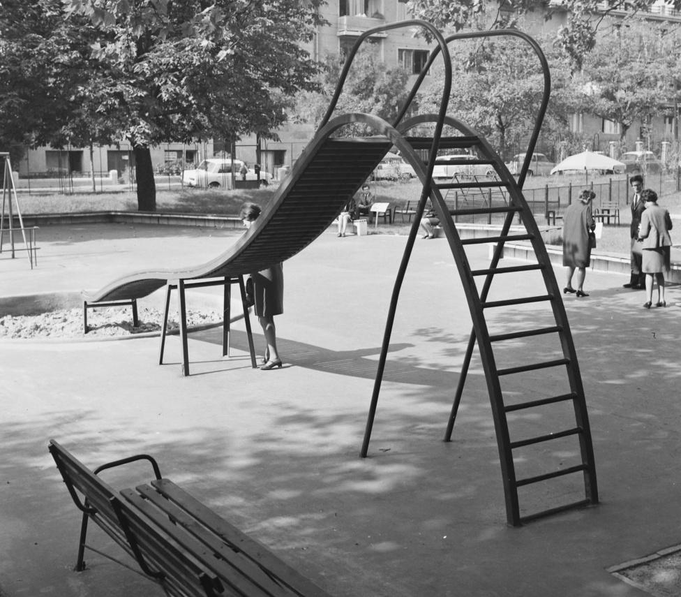 Janecskó Kata: A csepeli négyemeletes panelek közti kicsi játszótéren, épp szemben a ronda barnára festett földszinti erkélyünkkel volt egy majdnem pont ilyen csúszda-homokozó páros. Talán a csúszda és a célállomás méretarányai tették, hogy az ember kihívást támasztó célpontnak kezdte látni a homokozógödröt. Ezzel nagy gond nincs, egészen addig, amíg a csúszda áll. Nálunk egyszer egy szép napon nyoma veszett a lejtőnek, a - talán piros, talán sárga -  műanyagdarabnak, és ott maradtak csupaszon a vas létrafokok meg a vízszintes faléc, az elrugaszkodáshoz. A homokozó köré a játszótér gondos tervezői praktikus betonkaréjt építettek. Minden adott volt tehát életem első háromszoros zöldgallytöréséhez. Később már magam is hozzájárultam a környékbeli beton-fémjátszótereken a kedélyes balesetveszélyhez, szerettem apró gödröket ásni a homokozókba, és - a panelgyerekek ravaszságával - nejlonszatyor, kartondarab, miegymás meg vékony homokréteg segítségével álcázni azokat. Aztán csak várni, lesben.