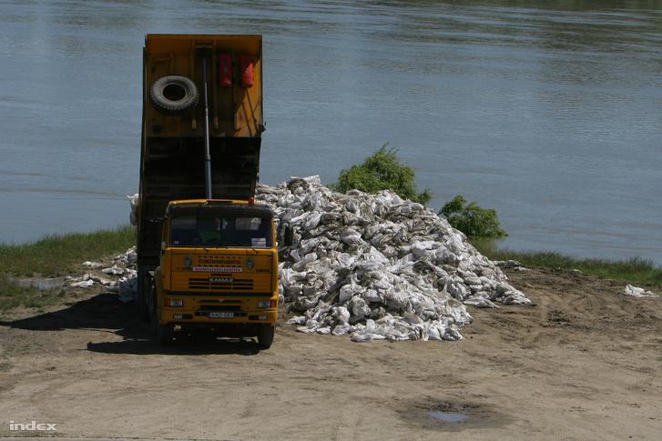 Elhasznált homokzsákokat tesz le egy teherautó a Római-parton