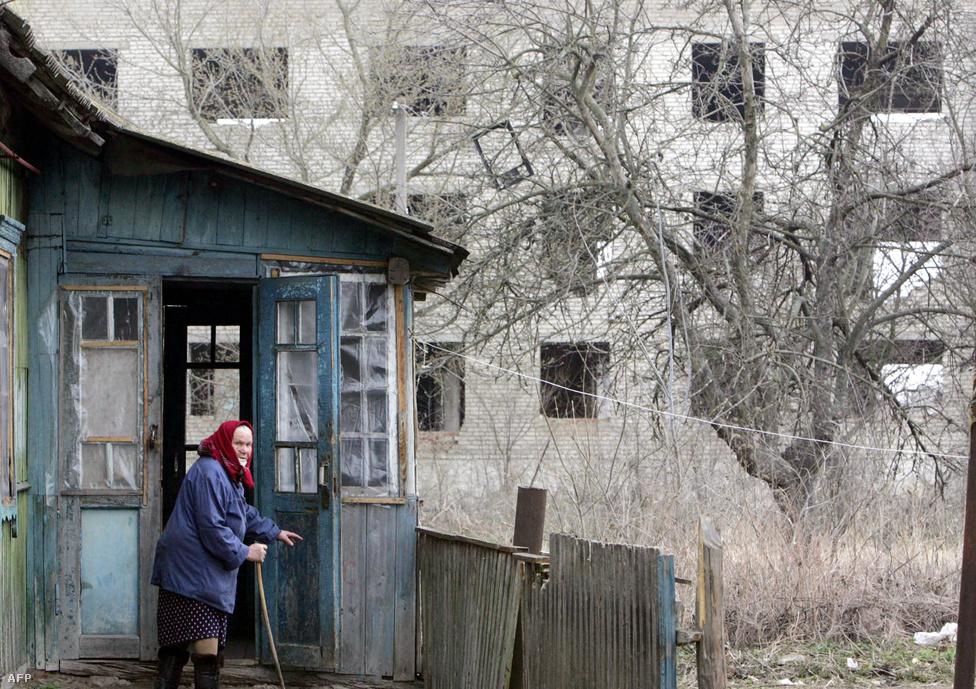 Egy idős nő áll a háza előtt 2006 áprilisában, a belarusz Sztrelicsevo falujában, mindössze pár kilométerre a 30 kilométeres zónától.  1986-ban a települést önkéntes alapon kiürítették, aztán lassanként visszaköltöztek az emberek: főleg oroszul beszélő emigránsok Ázsiából. A kormány hirdetésekkel csábította ide az embereket, akik közül sokan csak érkezéskor jöttek rá, mi vitte el innen az egykori lakosokat. Eredetileg 84 család költözött ide. Mivel pont a zóna határán vannak, nagyjából működik a civilizáció, hozzájutnak például áramhoz. Anno nagyon jól hangzott, hogy az akkoriban modernnek számító szovjet technológiát, traktorokat kapnak a földek megműveléséhez.