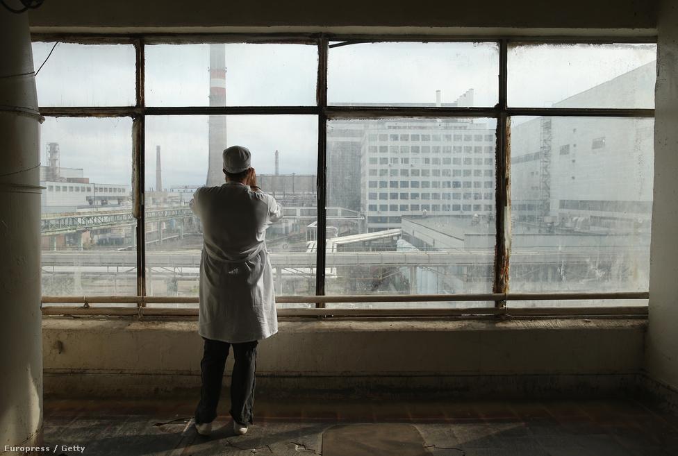 Csernobil ma már látványosság: ez a turista az egyes és kettes reaktorról készít fotókat az ablaküvegen át.