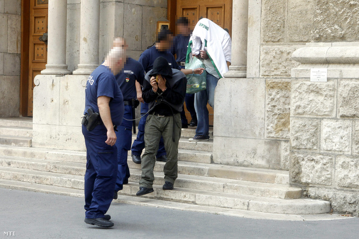 Rendőrök elvezetnek két férfit a Pesti Központi Kerületi Bíróság épületéből ahol döntöttek a gyanúsítottak előzetes letartóztatásáról 2012. július 28-án. A biztonsági őrként dolgozó férfiakat azzal gyanúsítják hogy 2011. december 3-án a Hajógyári-szigeten a Dokk nevű szórakozóhelyen illetve később az épületen kívül is bántalmaztak egy ittas 21 éves férfit majd az öntudatlan fiatalembert a Dunába dobták.