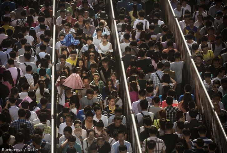 Kordonok között sorakoznak az utasok egy forgalmas metrólejárat előtt Pekingben.