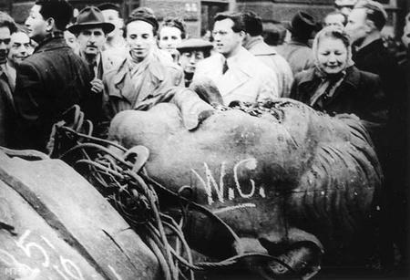 Baltával, csákánnyal törik darabokra az október 23-án ledöntött Sztálin-szobrot. Darabjait a forradalom emlékeként viszik el az arrajárók.